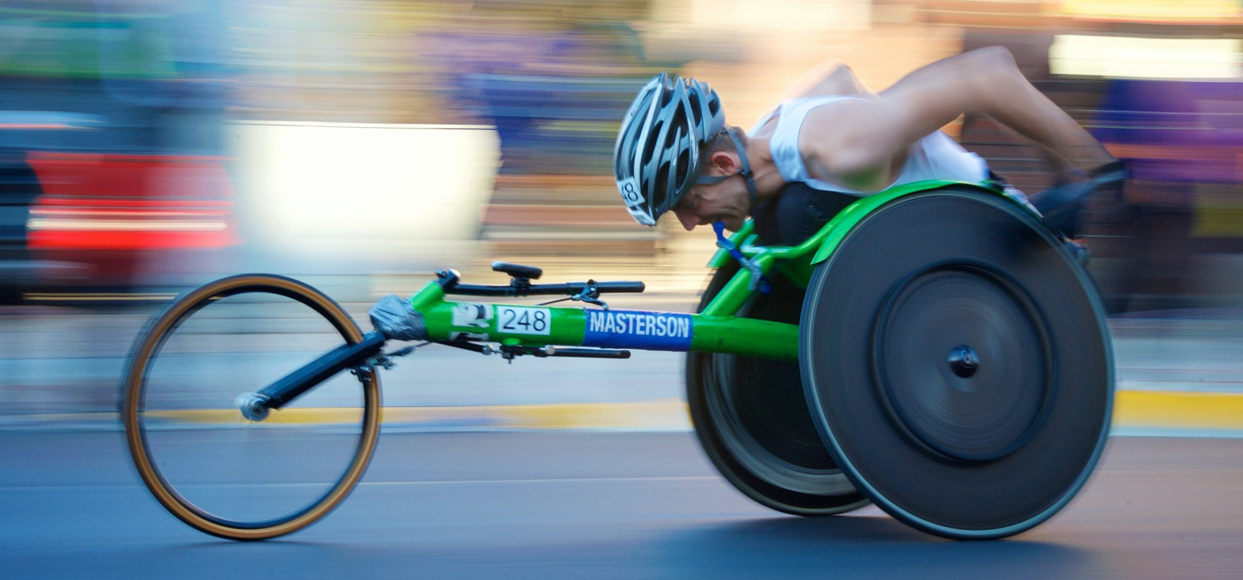 man riding green racing wheelchair